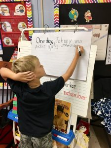child writing on an easel