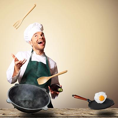 man juggling cooking utensils