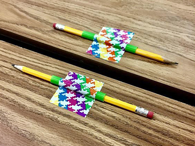 pencils taped to a desk