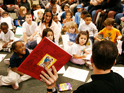 man reading books to childrens class